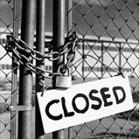 A sign indicating that the factory behind the gate on which it rests has been shuttered