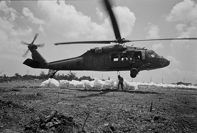 National Guard helicopters drop 3000-lb. sandbags to build up an artificial berm.